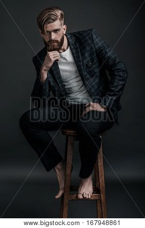 Thoughtful handsome. Full length of stylishly dressed young man looking at camera and holding hand on chin while sitting on chair against grey background