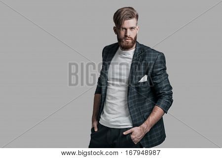 Ready to go! Handsome man with long hair and beard looking at camera while standing against grey background
