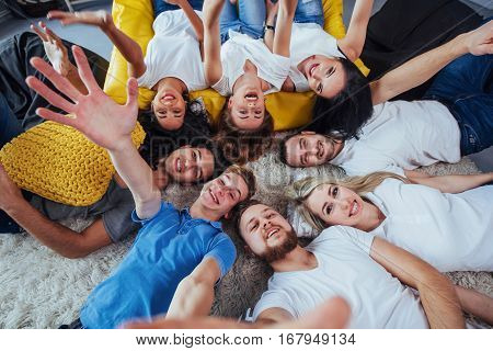 Group beautiful young people doing selfie lying on the floor, best friends girls and boys together having fun, posing emotional lifestyle people concept.