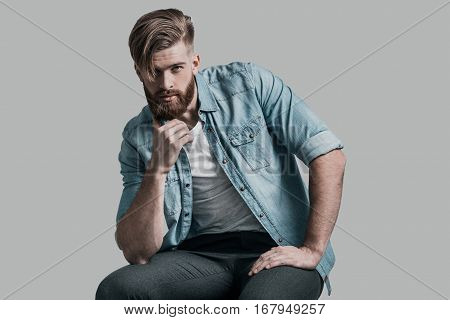 He knows all your secrets. Young man looking at camera and holding hand on chin while sitting on chair against grey background