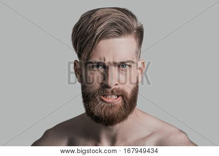 Making a face. Portrait of young man making a face and looking at camera while standing against grey background