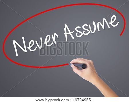 Woman Hand Writing Never Assume With Black Marker On Visual Screen.