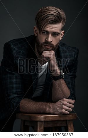 Stylishly confidence. Handsome young man in casual clothing looking away while leaning on stool against grey background