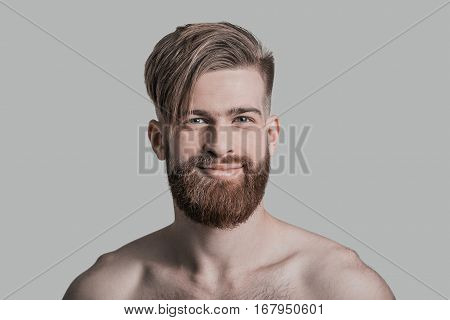 Smiling handsome. Portrait of handsome man looking at camera and smiling while standing against grey background