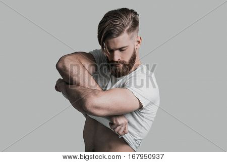 Too sexy for his clothes. Young man taking off his T-shirt while standing against grey background