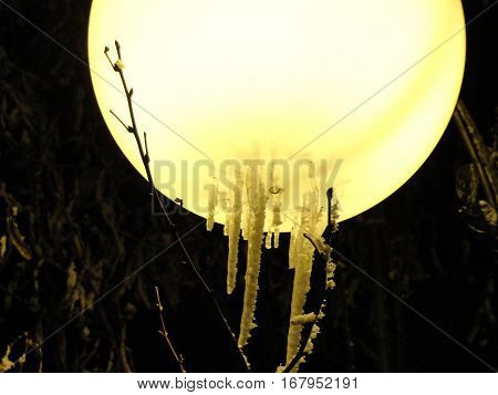 Night. Light. Winter. / Close-up of the yellow lantern on a black background that overgrown by icicles.