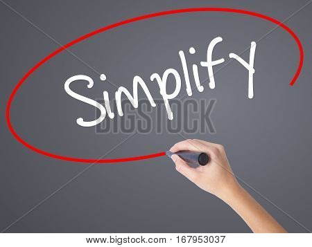 Woman Hand Writing Simplify With Black Marker On Visual Screen