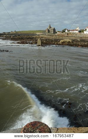 A wave crashes against the breakwater at St. Monans harbour
