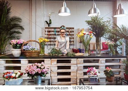 Smiling attractive young woman florist standing and working in flower shop