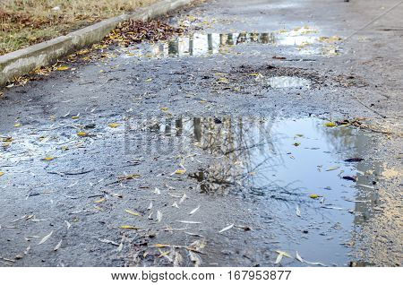 crack asphalt with puddles and potholes close up