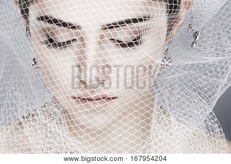 A beautiful girl is in a white veil, isolated on a light - grey background, emotions, cosmetics