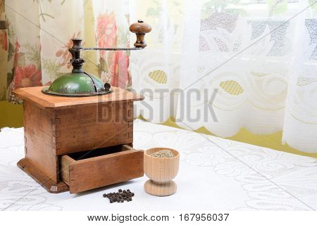 Peppercorns and ground pepper with a retro mill on the table by the window.