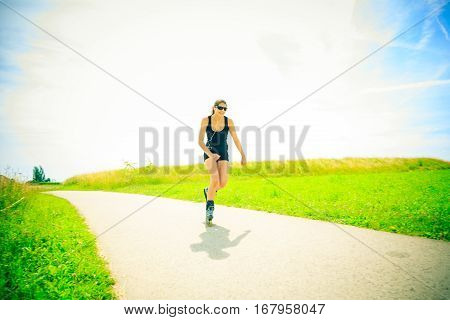 young woman with inline skates, skating in a park