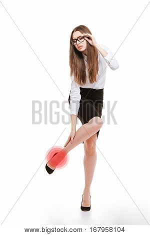 Full length portrait of a young business woman holding her hurting ankle isolated on a white background
