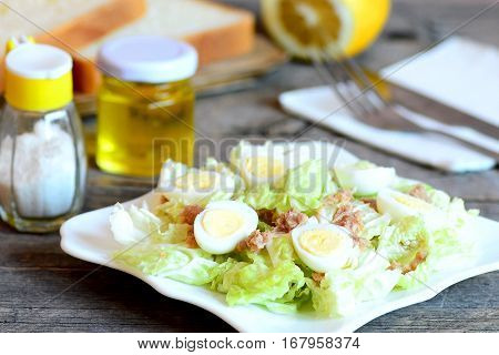Salad with napa cabbage, quail eggs and canned tuna fish. Cabbage salad on a plate, fork, knife, olive oil bottle, salt shaker, lemon, bread pieces on rustic wooden table. Easy starter recipe. Closeup