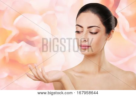 Beautiful indian girl with perfect skin and makeup. Beauty and health care concept. Ideal face of brunette, isolated on pink background with copy space and hand holding or showing something