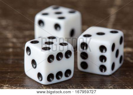 Three white dice on dark wooden background