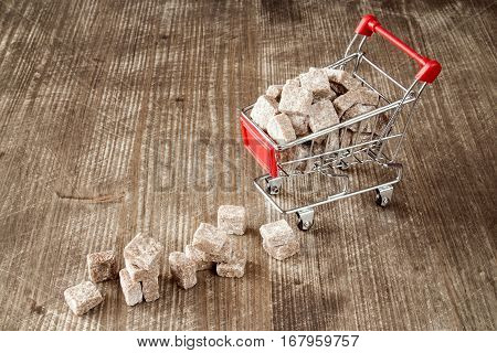 Shopping cart with brown cane sugar on wooden background