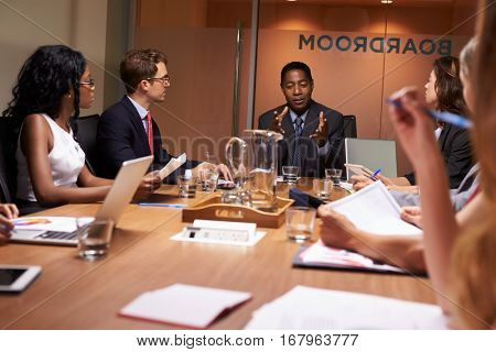 Businessman addressing colleagues at a meeting, close up