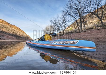 FORT COLLINS  CO, USA - JANUARY 22, 2017: Winter stand up paddling - All Star racing paddleboard by Starboard on a shore of Horsetooth Reservoir.