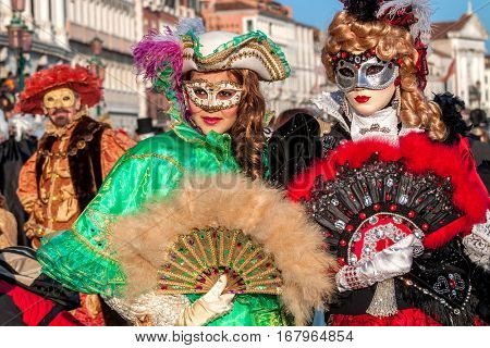 VENICE, ITALY - MARCH 04, 2011: Two young women at San Marco square wear colorful dresses and masks during traditional famous Carnival taking place each year in Venice.