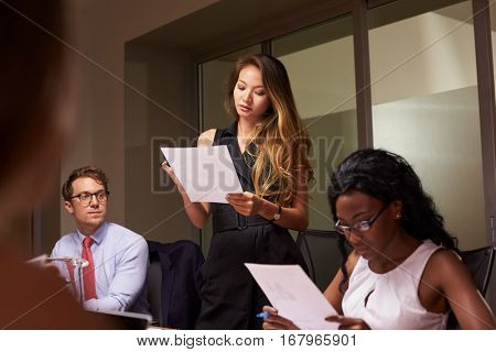 Woman stands reading document at an evening business meeting