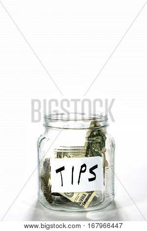 Glass money jar labeled tips has a few dollar bills in it.