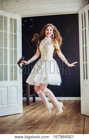 Fashion photo of young beautiful girl wearing wedding dress. Happy jumping bride. Professional make-up and hairstyle. Perfect skin. Fashion photo. Baby doll style.