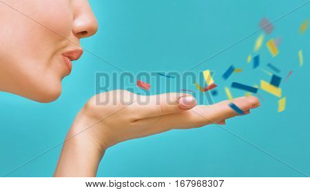 Young woman on background of bright blue wall. Girl blowing multicolor confetti. Close up.