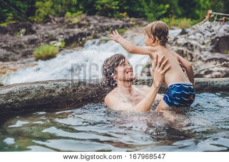 Geothermal Spa. Father And Son Relaxing In Hot Spring Pool Against The Background Of A Waterfall