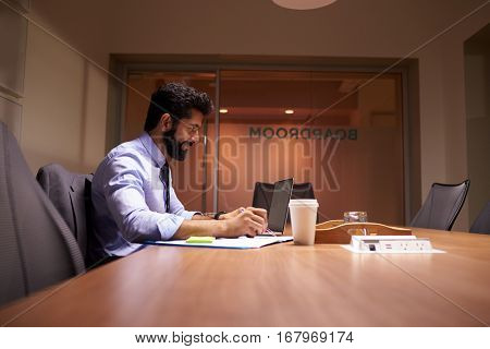 Middle aged Hispanic businessman working late in an office