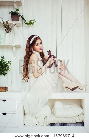 Fashion photo of young beautiful girl wearing wedding dress. Happy smiling bride. Professional make-up and hairstyle. Perfect skin. Fashion photo. Baby doll style. Natural beauty.