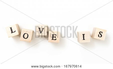 Wooden Cubes With Words Love Is, On White Background.