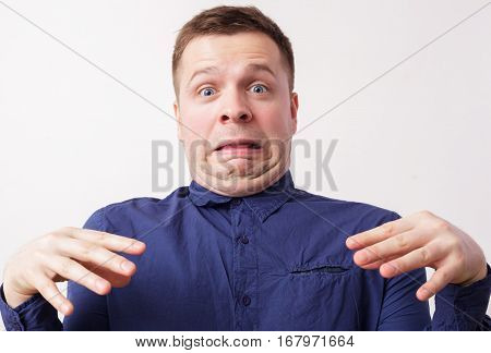 Young Man In A Blue Shirt In Disgust. Double Chin Wrinkles