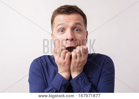 Young Man Screaming In Fear, Clenching His Fingers At The Mouth. Scared Of Bad News