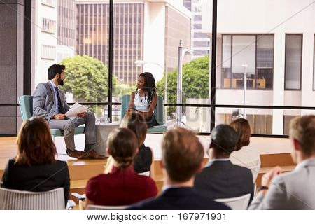 Male and female speakers in front of audience at a seminar