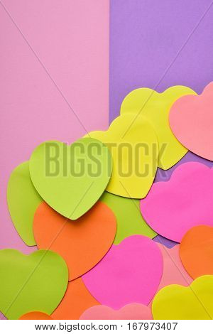 some heart-shaped sticky notes of different colors with a blank space, on a half pink and half violet background
