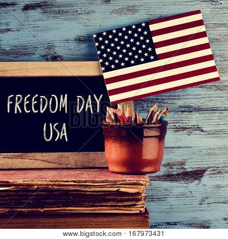 the text freedom day usa written in a chalkboard placed on a pile of old books, next to a pot with pencils and a flag of the United States, against a blue rustic wooden background