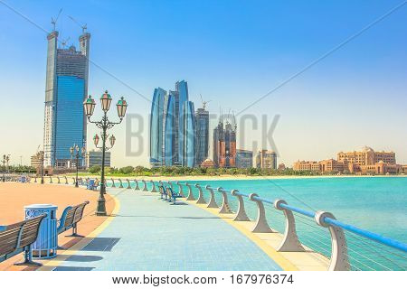 Dhabi skyline from cycle paths of Corniche. Abu Dhabi, United Arab Emirates, Middle East. Modern skyscrapers and landmark on background. Summer holidays concept.