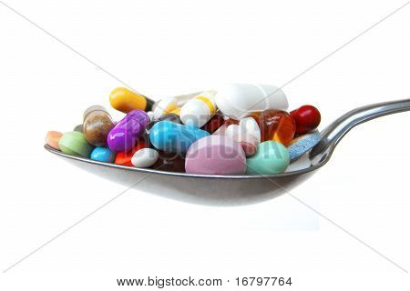 Large metal spoon heaped with a colorful mix of pills, tablets and capsules in different shapes and sizes. Isolated against a white background. May be used to illustrate general health topics or drug abuse issues including self-medication, dietary problem poster