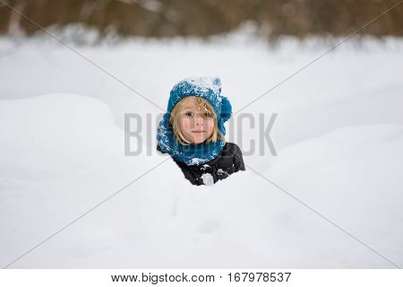 Portrait of adorable little kid boy with long blond hair playing with snow outdoors. Child with blue scarf and hat walking and having fun on a windy winter day.