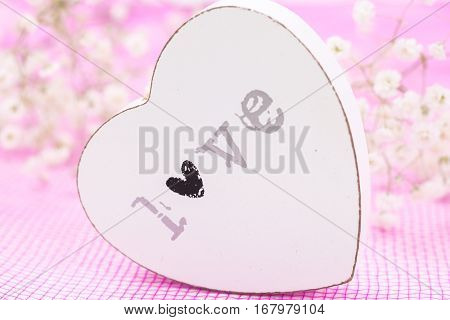 White Wooden Heart Closeup With Word Love, On Pink Mesh Fabric And White Flowers Blurred Background.
