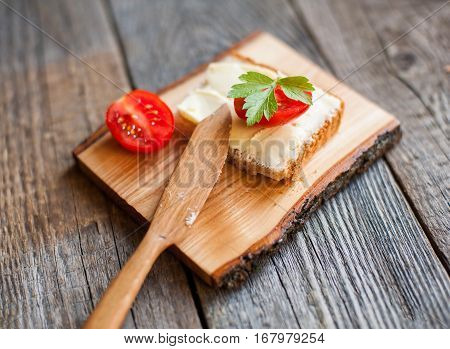 handcarved wooden butter knife with light breakfast