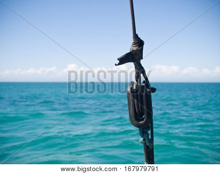 metal rigging anchor on a yacht boat with a green sea and blue sky backdrop