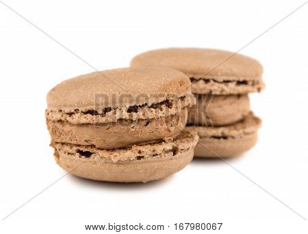 Two brown french macaroon cookies on white background
