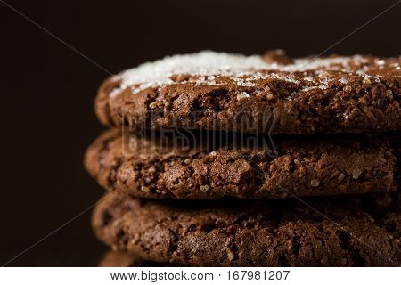 Stack of Chocolate chip cookies on brown background. Stacked chocolate chip cookies shot with selective focus.