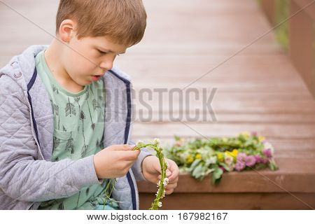 Portrait of cute kid boy sitting on wooden bridge and weaving a wreath of wild flowers. Child making flower wreath. Lifestyle and summer concept