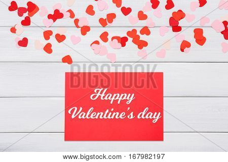 Valentine day letter. Card with red hearts above it on white wood background. Lover's holiday confession or proposal concept