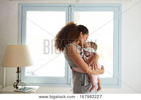 Mother Cuddling Baby Daughter At Home In Front Of Window
