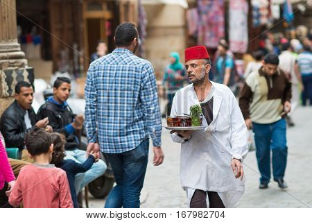 CAIRO, EGYPT - MARCH 13, 2016: A tea house servant serves tea at historical Khan El-Khalili Souq marketplace which is one of the important tourist magnets in the Capital City Cairo, Egypt.